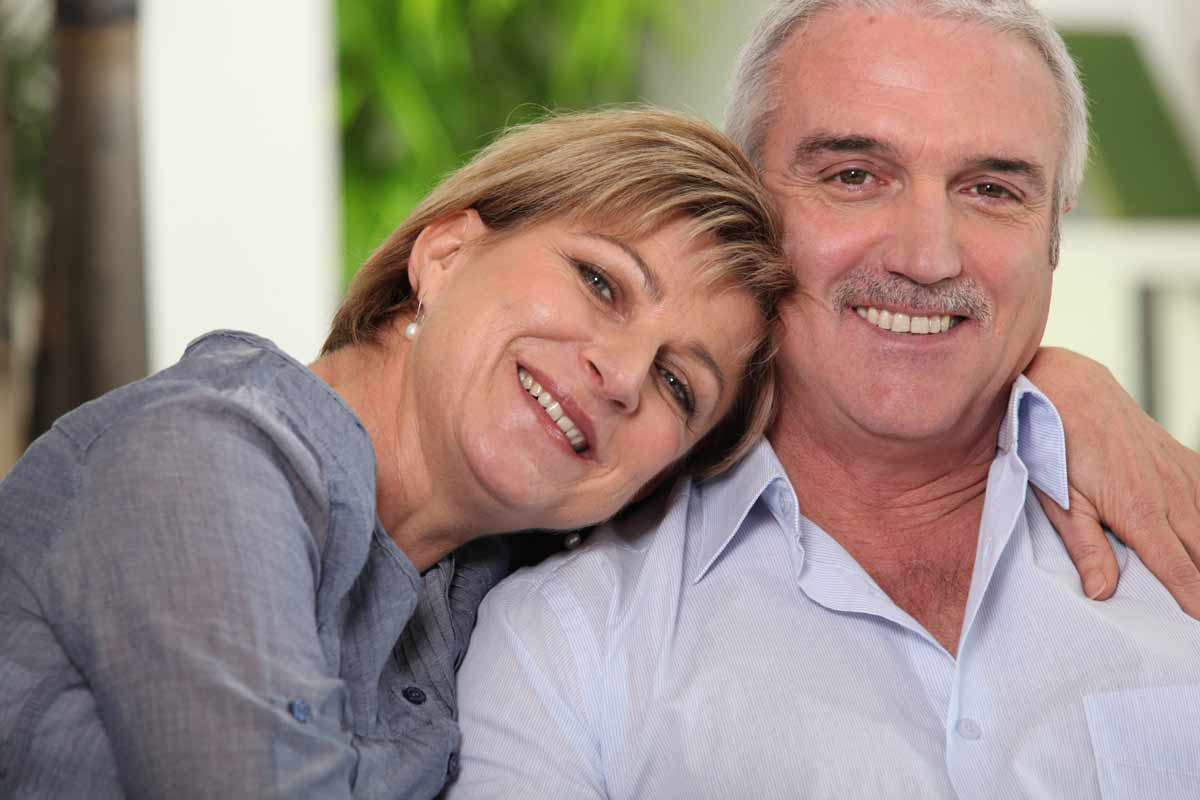 Couple in their 50s looking at the camera and smiling.