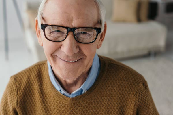 Elderly man with glasses looking at the camera.