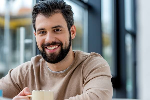Ethnic man at a coffee shop.He's facing forward and smiling.