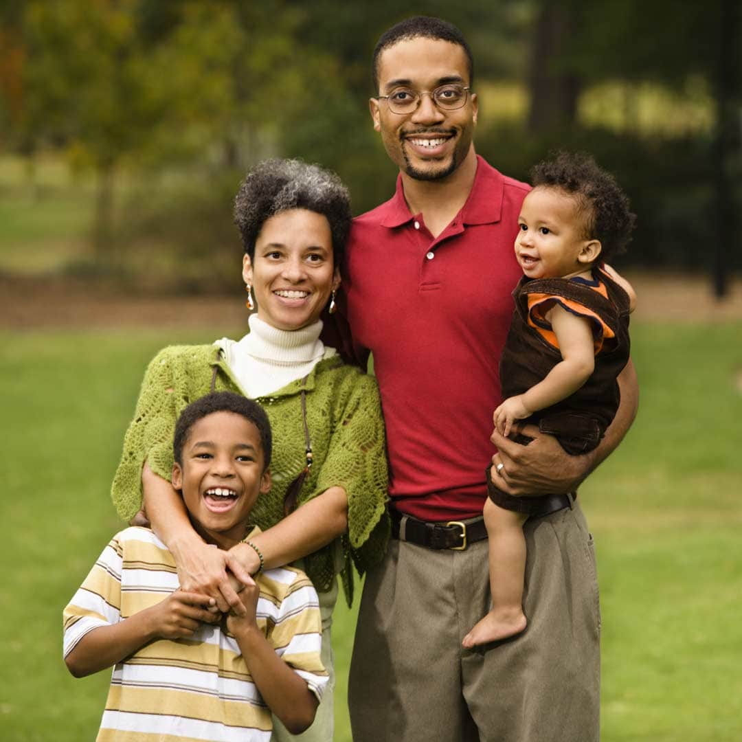 Black family of four in the park. They are posed as if they are taking a family portrait.