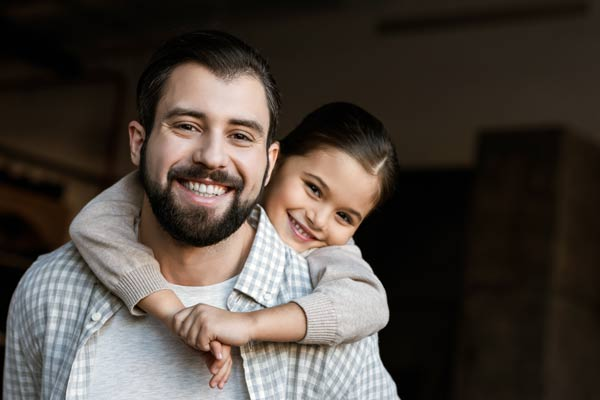 Bearded man with his young daughter on his back, piggy back style. They are both facing the viewer and smiling.