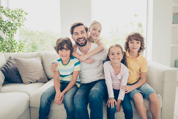 Happy dad with four children sitting on their couch. They are all sitting on the couch facing forward. The youngest daughter is on his back, piggy back style.