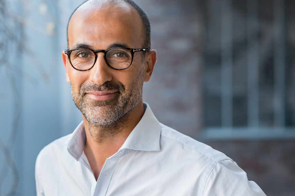 Balding middle aged ethnic man with glasses and beard stubble. He's wearing a white collared shirt and looks professional.