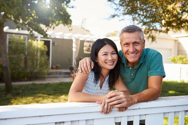 Middle aged couple leaning on their front gate. Their house is in the background.