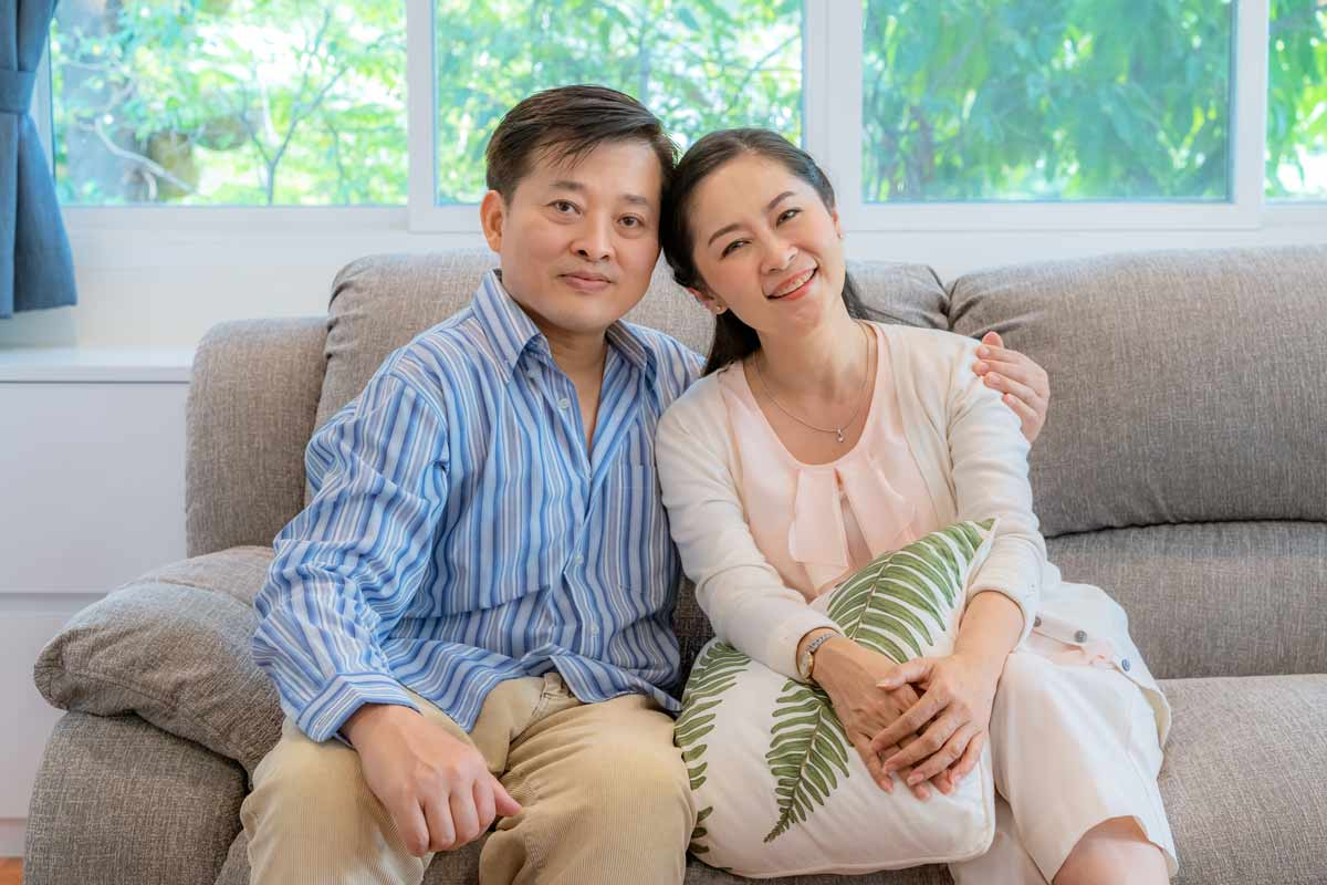 Asian couple in their 50s sitting on the couch. They are both posing for the camera and have a pleasant look on their face.