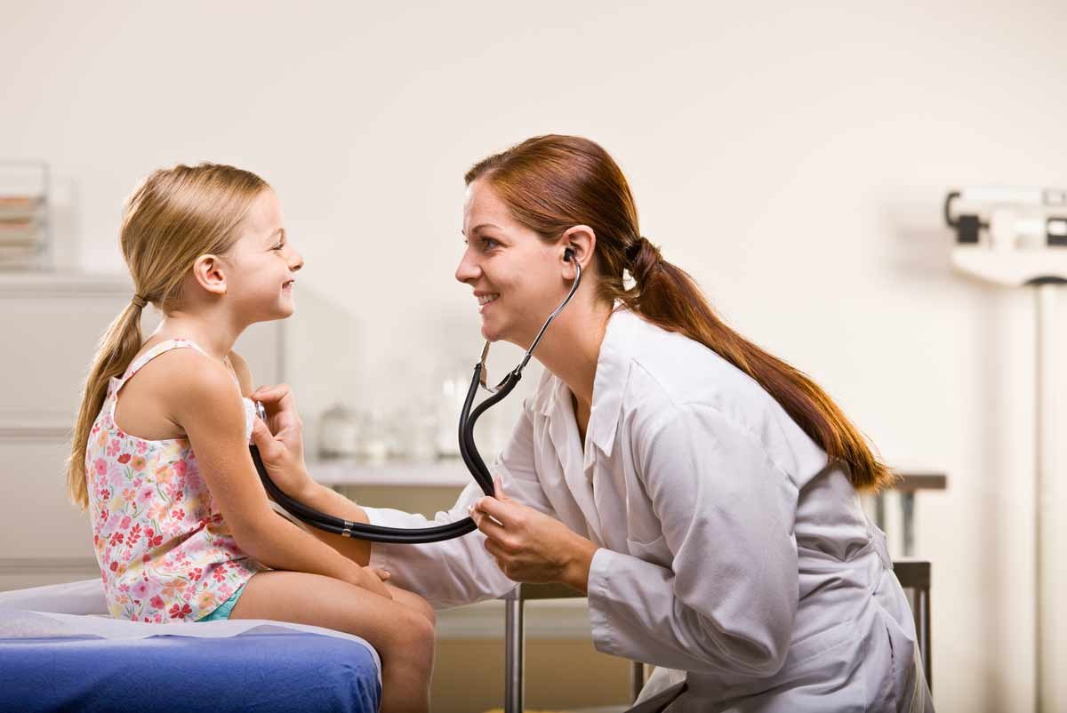 Woman doctor holding a stethoscope to a tween girl. They are in her office and both of them are smiling.