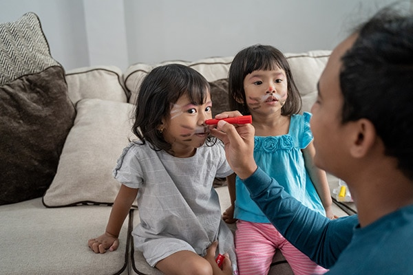 Father putting face paint on both his young daughters.